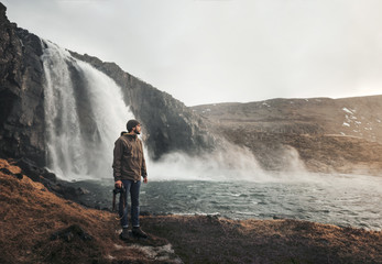 Young man standing near waterfall with camera