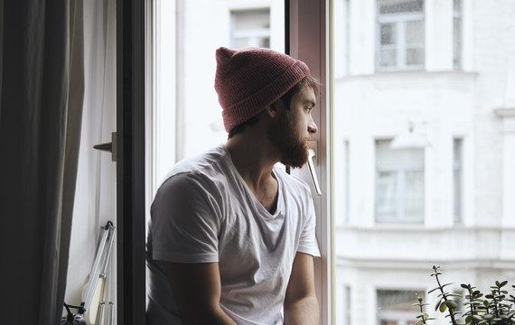 Thoughtful young man sitting near window