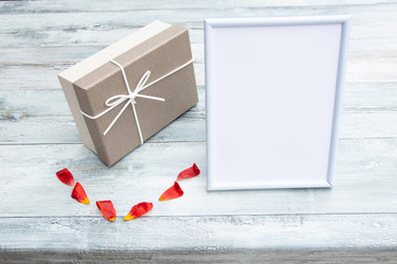 Gift box with a white picture frame with place for your text and tulip leaves on rustic bright wooden table. Card concept.