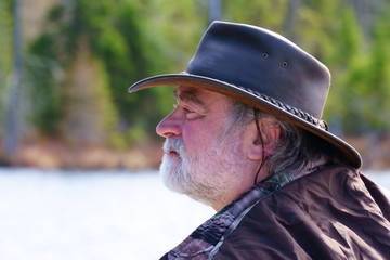 A peaceful caucasian man, 50's, wearing a white beard, a leather hat Australian style and a camouflage coat, is fishing in his boat on a lake with blue water by a beautiful, fresh, sunny morning in th