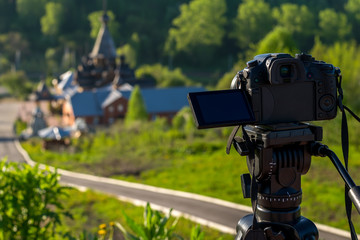 camera on a tripod shoots a wooden Church in the early morning