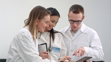 Three smiling doctors discussing X-ray while using tablet