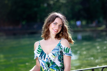 Portrait of a young woman by the green lake, in the park outdoors.