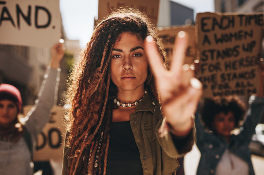 Woman showing a peace sign during protest