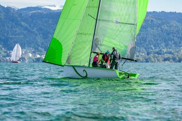 Wall Murals Sailing Racing sailboat with green spinnaker sailing a regatta at lake constance