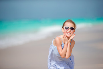 Beautiful little girl in dress at beach having fun.