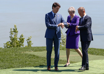 Leaders look at their watches as they pose for family photo at the G7 Summit in La Malbaie