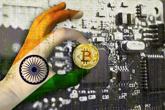 Bitcoin crypto currency India flag Binary code Golden Coin of Bitcoin in the Indian flag hand between two fingers shows OK sign on a chip background with matrix effect