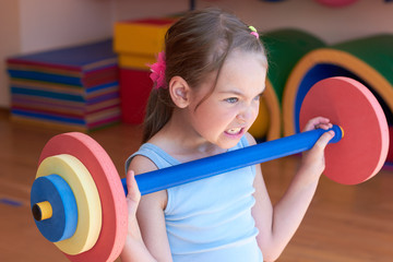 The child raises a heavy barbell in the gym.