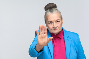 Old woman showing stop sign at camera