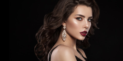 Fashion glamorous portrait of a girl on a dark background. Elegant hairstyle, bright makeup and lip color. Hollywood picture.