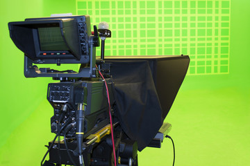 Broadcast television studio camera in green screen studio room with LED lights on the ceiling.