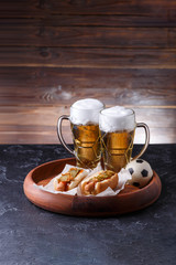 Picture of two mugs of beer and hot dogs on wooden tray