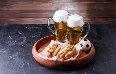 Photo of two glasses of beer and hot dogs on wooden tray with football