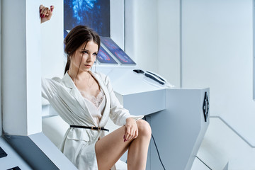 Futuristic white interior reminiscent of a laboratory or a spaceship. Beautiful brunette in white clothes with blue eyes posing for the camera Fototapete