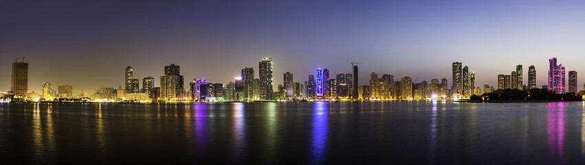 Panoramic view of Sharjah waterfront cityscape in UAE at dusk