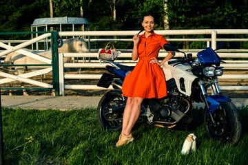 Beautiful brunette girl with pigtails, in a red dress in good weather with milk and on a motorcycle. On the background of the farm with green grass and a beautiful sunset. Walking around the horse