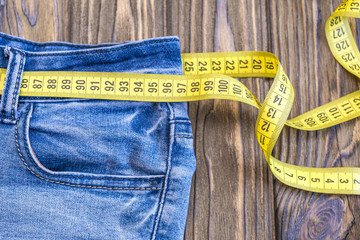 Healthy lifestyle and nutrition concept. Blue jeans with a measuring tape instead of a belt. Close up of jeans with a measuring tape around the waist. wooden background. Diet, sports, weight loss.