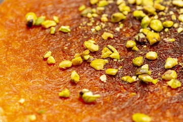 Arabic dessert kunefe , slide with pistachio, turkish kunafa, kadayif with cheese hot eaten a sweet