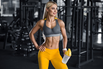 Fitness woman with shaker in gym, drinking water. Athletic girl, shaped abdominal, slim waist