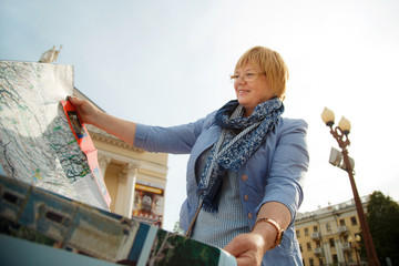 Happy female tourist looking at city map