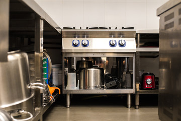 All steel industrial kitchen with burners and utensils