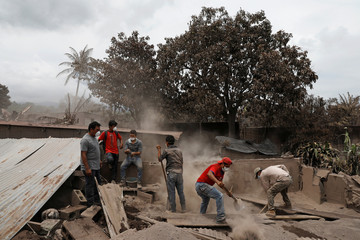 People work in an affected area after the eruption of the Fuego volcano in Escuintla