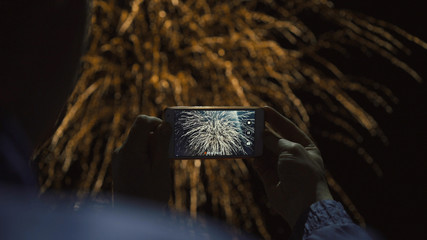 Silhouette of a man photographing fireworks at night sky. Beautiful salute in honor of the holiday.