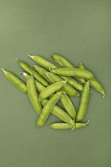 Green pea pods on a green background