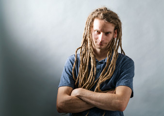 Man with dreadlocks with arms folded on a dark background