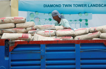 A labourer unloads cement bags from a truck at a construction site in Phnom Penh