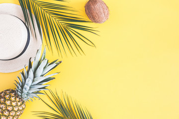 Summer composition. Tropical palm leaves, hat, pineapple, coconut on yellow background. Summer concept. Flat lay, top view, copy space