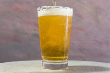 Glass of beer on a dark-red background