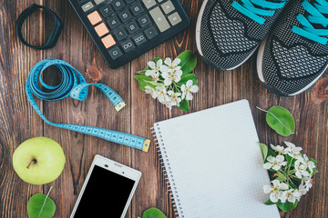 Fitness, healthy and active lifestyles concept. Sport shoes, smartphone, tape, calculator, fitness bracelet and green apple on wooden background with copy space. Top view