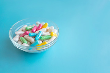 Nootropics, smart drugs, cognitive enhancers, compounds enhance brain function, Improve memory, cognitive and particularly executive functions. Multicolored capsules in female hand on blue background