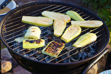 Zucchini on the lattice over the coals in a round grill
