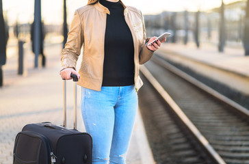 Woman using smartphone in train station while waiting in the platform. Lady with suitcase and luggage holding mobile phone.