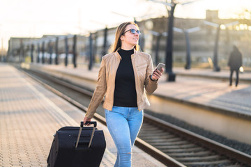 Confident business woman pulling suitcase and holding mobile phone in train station. Smiling lady walking in platform and using smartphone. Female traveler arrived to destination.
