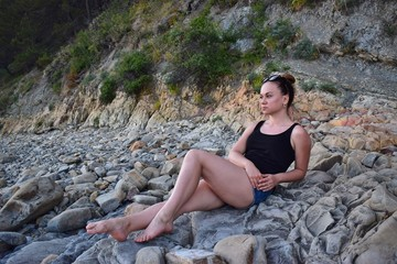 Girl in shorts and a t-shirt with glasses resting on a rocky shore.