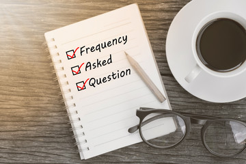 Frequency Asked Question and check list marks in notebook with glasses, pencil and coffee cup on wooden table. FAQ concept.