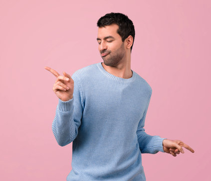Handsome man listening to the music and dancing on pink background