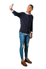Young african american man taking a selfie with the mobile on isolated white background. Ideal for use in architectural designs