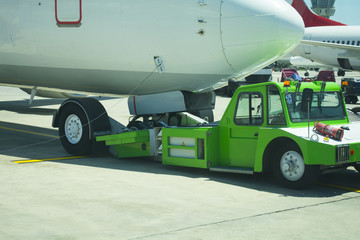 Large aircraft being pulled by airport tug tractor taxing on airfield into docking position for passenger boarding the airplane