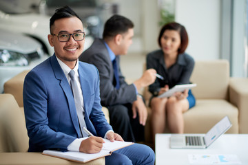 Portrait shot of handsome Asian car dealer wearing elegant suit looking at camera with wide smile while distracted from working meeting at showroom