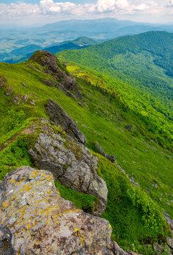 boulders along the mountain ridge. location Pikui mountain. Borzhava mountain ridge in the far distance on the horizon. Beautiful summer landscape of Carpathian mountains