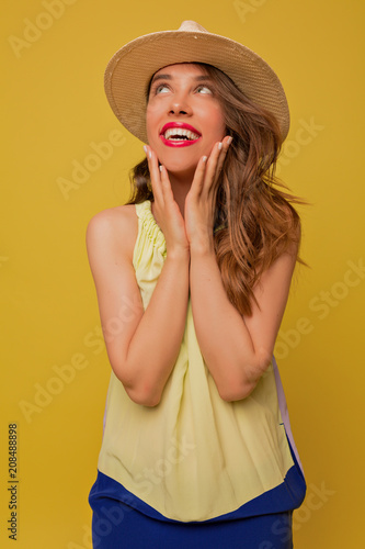 4514e4617fd7 Romantic lovely young woman with long hairstyle holding hands on the face  and posing with surprised smile, looks aside. Indoor portrait of emotional  female ...