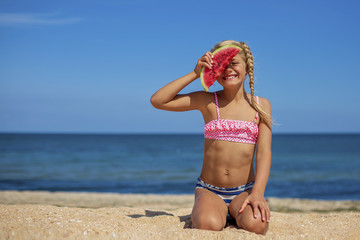 Portrait of a pretty blonde little girl in swimsuit eating watermelon on sandy beach near the sea on sunny day. Health eating. Sport and recreation