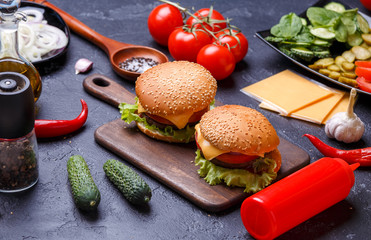 Photo of two hamburgers on wooden board, cheese