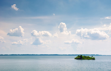 island on the lake zemplinska sirava. beautiful landscape of Slovakia. calm summer day with beautiful cloudscape on the sky. lovely minimalist background