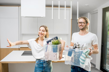 Young and happy couple holding boxes with different home stuff moving to a new modern house